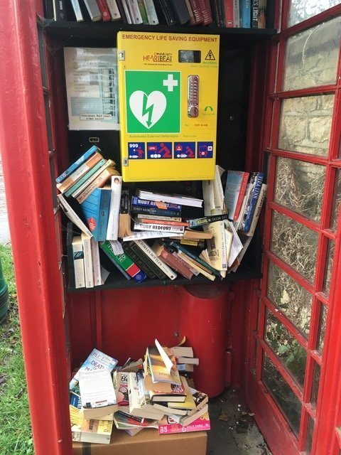Sunningwell telephone box cluttered with books